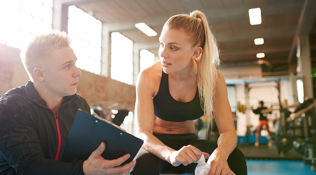 Shot of a personal trainer and young woman discussing fitness plan. Personal trainer showing something on clipboard to student in the gym.