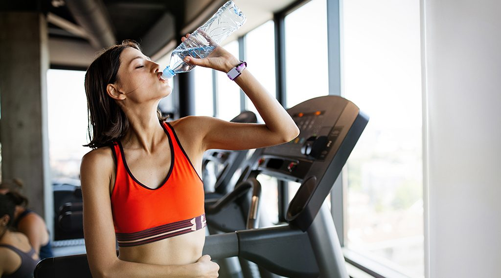 Refreshing after workout. Beautiful young woman drinking water to stay hydrate in gym